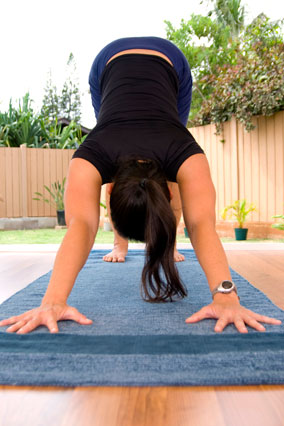 Woman doing downward-dog yoga pose on mat