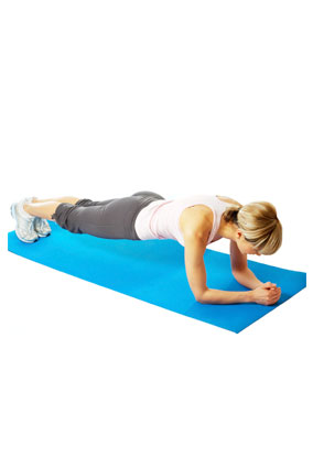 Woman doing plank exercise on mat