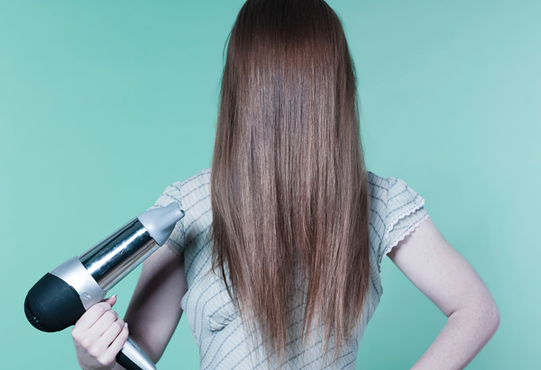 Woman with hair over face, pointing blow-dryer at head