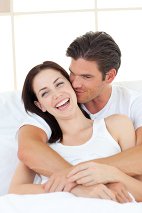 Couple laughing together in the bedroom