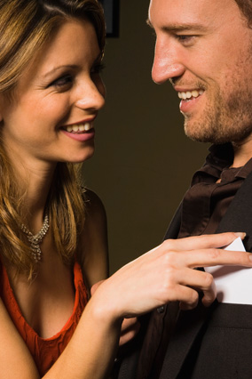 Woman putting business card in man's pocket