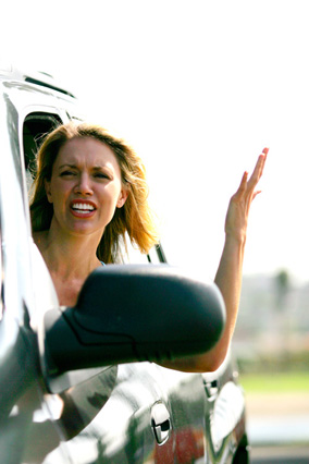 Frustrated woman leaning out of car window