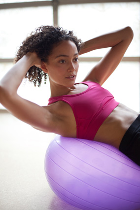 woman doing abdominal exercises on a stability ball