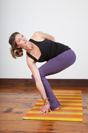 woman doing yoga twist in a studio