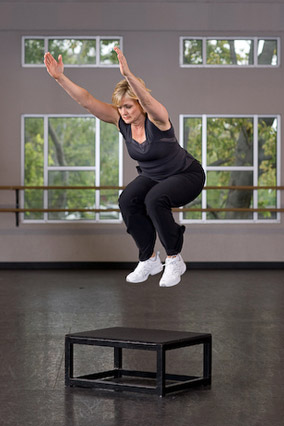 woman doing box jumps at the gym