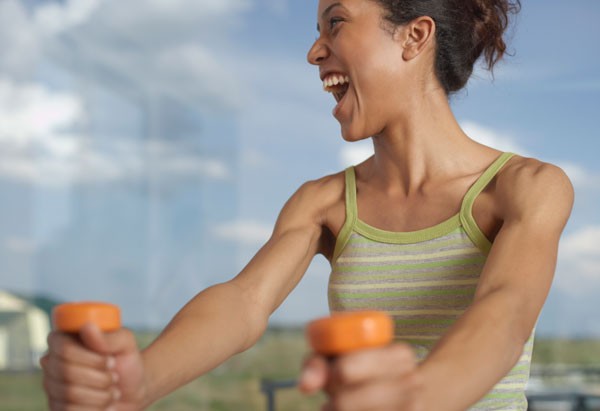 woman smiling while using arm weights