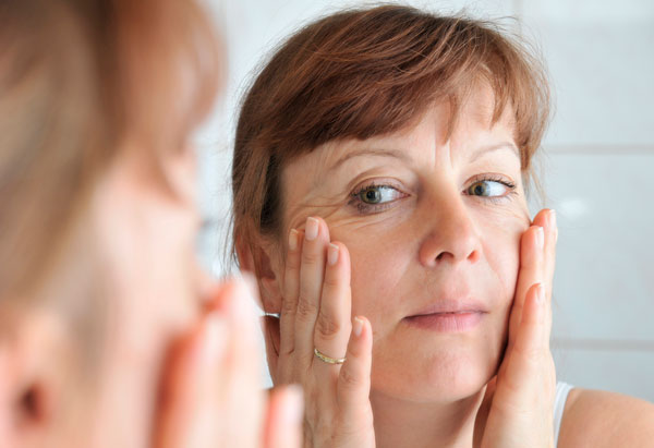 stressed woman examinging her face in mirror