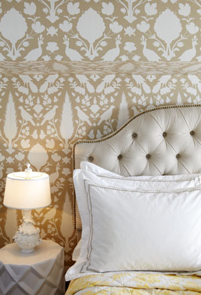 gold and white wallpaper with white headboard
