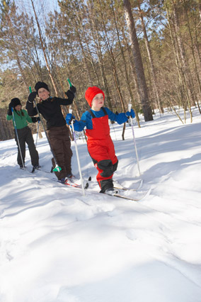 Young children cross-country skiing through the woods
