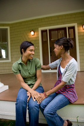 Two women talking together on porch