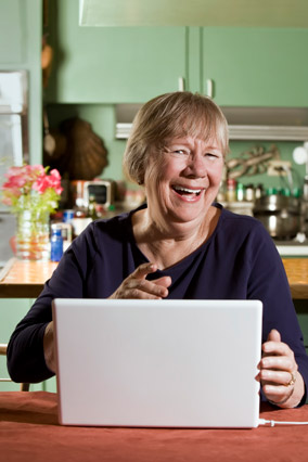 Woman laughing while looking at laptop