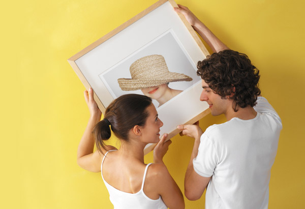 Couple hanging a matted frame