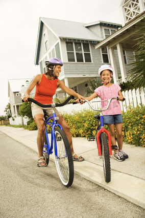 Mentor and child ride bikes