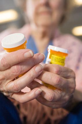 Older woman with prescription medication bottles