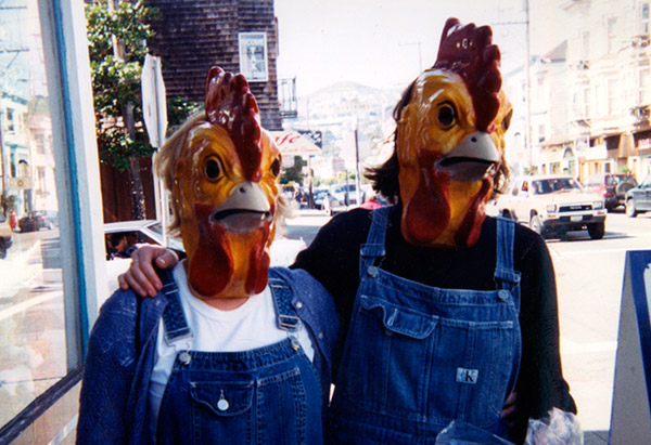 Couple wearing chicken masks and overalls