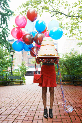 woman in trumpet skirt carrying a birthday cake