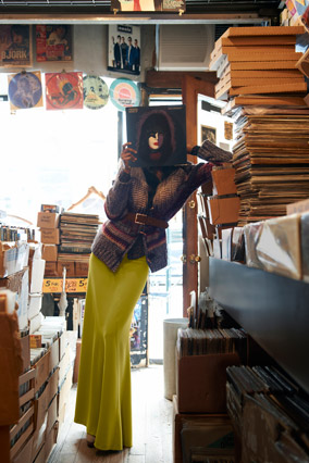 woman looking at a record wearing a maxi skirt
