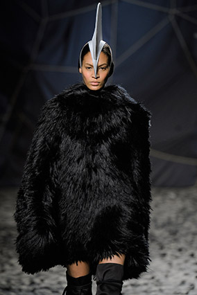 Runway model wearing large black fur and dorsal fin on head