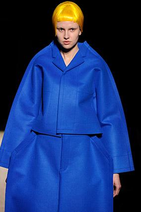 Runway model wearing oversize blue coat