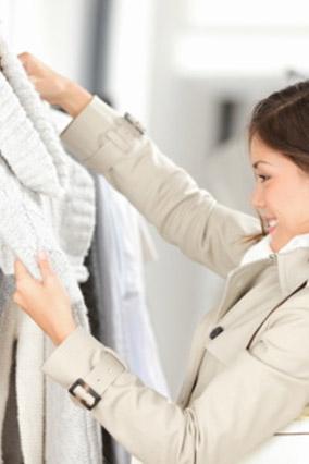 Woman examining gray cardigan on clothing rack