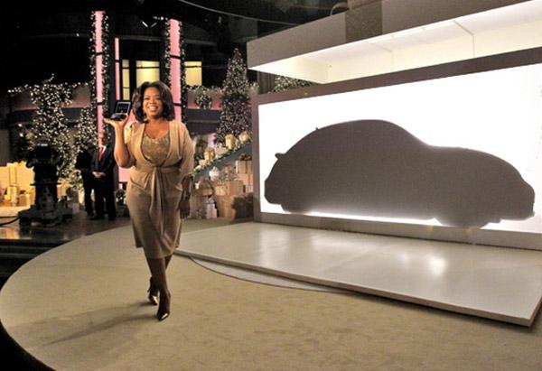 Oprah Winfrey in front of silhouette of Volkswagen Beetle