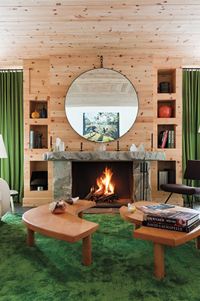 A modern-meets-rustic living room featuring wood-paneled walls and emerald curtains