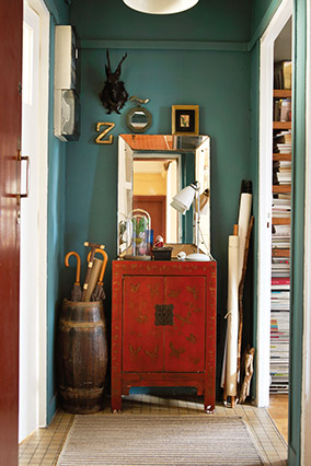 Teal/emerald entryway with a red cabinet and distressed mirror