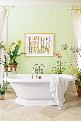 Pale green bathroom with freestanding bathtub, surrounded by potted plants