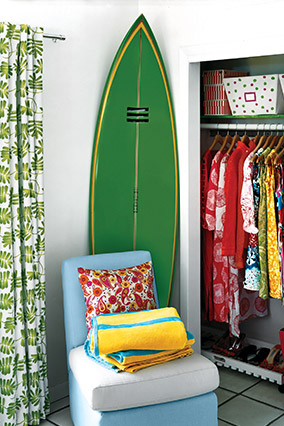 White room with green surfboard and other green accessories