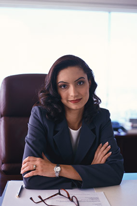 Woman executive sitting behind desk, arms folded