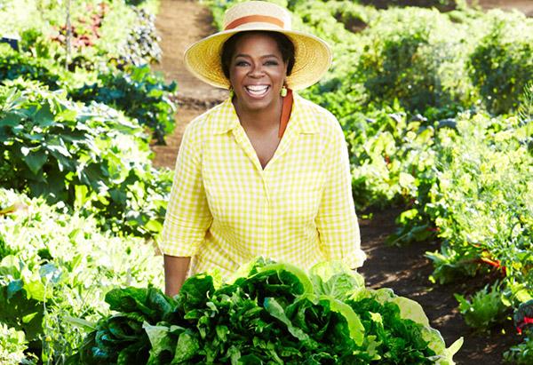 Oprah pushing a wheelbarrow