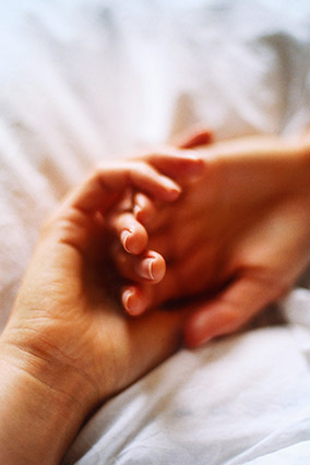 Couple holding hands in bed
