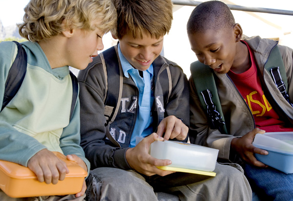 Classmates anticipating what is inside their lunch bag
