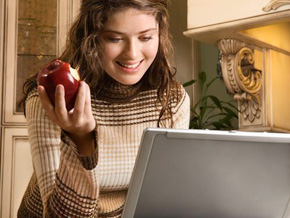 Woman eating an apple while on a computer