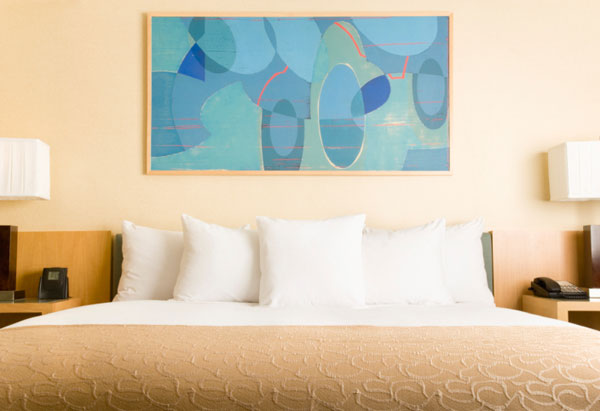 Turquoise painting above neutral bed