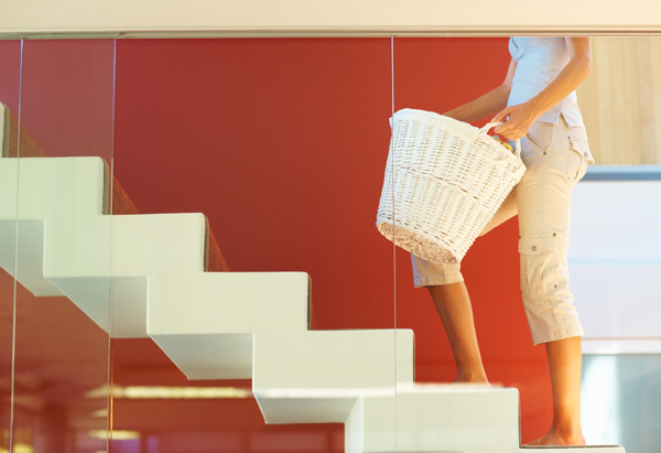Woman carrying laundry basket up the stairs