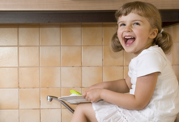 Girl having fun and washing dishes