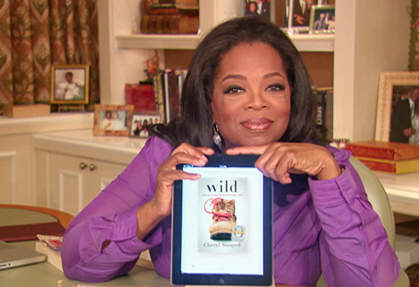 Oprah holding iPad with the book Wild by Cheryl Strayed