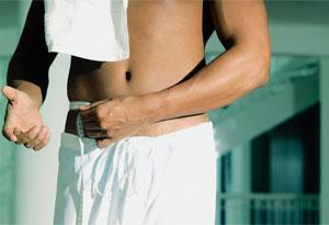 shirtless man measuring his waist