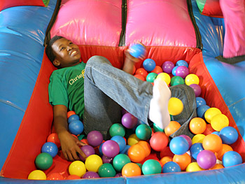 A child enjoys playing at the Christmas carnival.