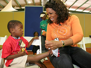 Oprah helps a child with his new shoes.