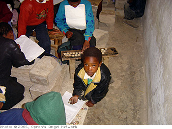 Some children use cement blocks as desks.