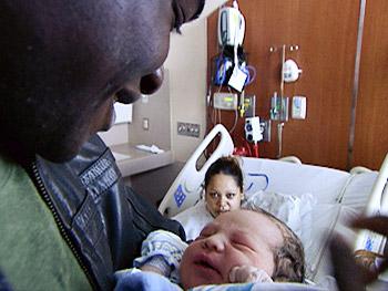 Sheg holds a newborn at Denver Health's Newborns in Need.
