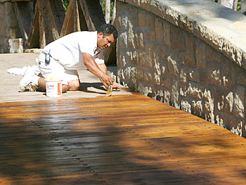 A worker stains and seals the bridge.
