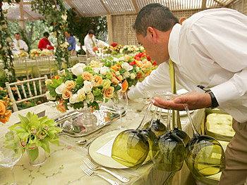 A staff member helps set the table.