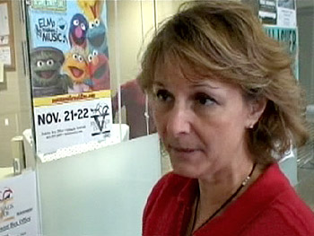 Mary Schmit in front of a poster for 'Sesame Street Live'