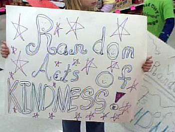 Before helping to carry groceries to cars, Brownies hold up signs they made.