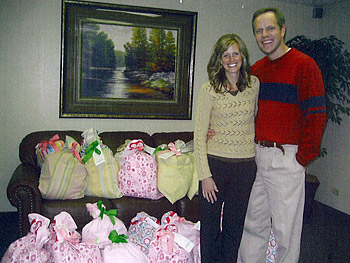 Mindy and her husband with the 'Pillows of Love' created for birth mothers of adopted children