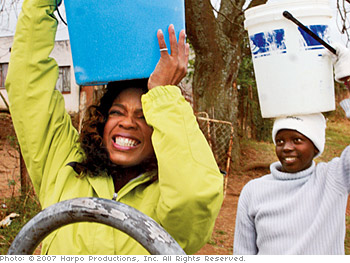 Oprah tries a South African girl's chore.
