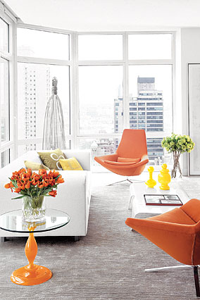 The Rubins' living space features orange armchairs and a stain-resistant white couch.